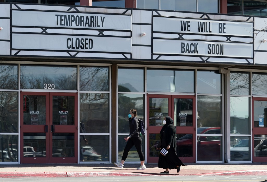 Shoppers pass a theater closed due to the COVID-19 outbreak, Wednesday, March 3, 2021, in San Antonio. Gov. Greg Abbott says Texas is lifting a mask m...