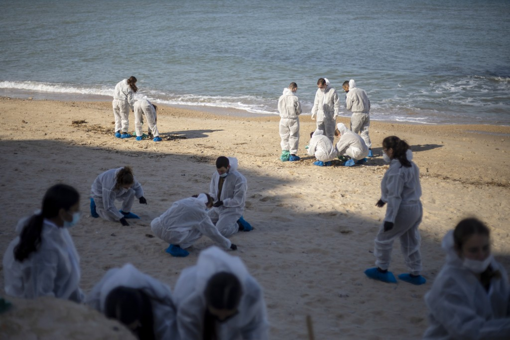FILE - In this Monday, Feb. 22, 2021 file photo, Israeli soldiers wearing protective suits clean tar from a beach after an oil spill in the Mediterran...