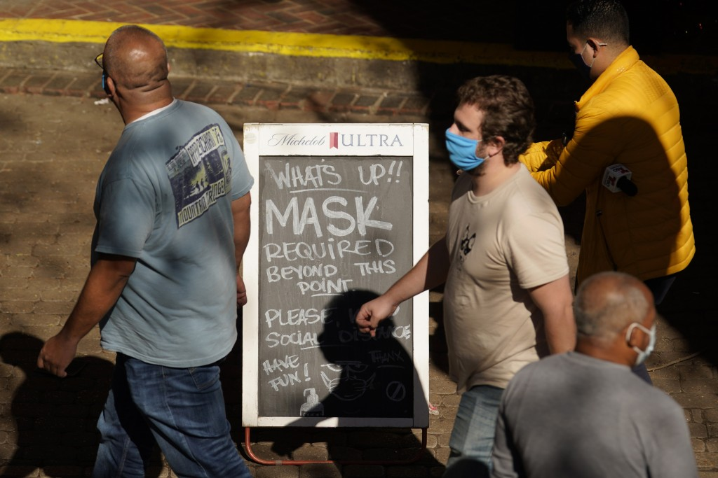 Visitors wearing face masks walk past a sign requiring masks at a restaurant along the River Walk, Wednesday, March 3, 2021, in San Antonio. Gov. Greg...