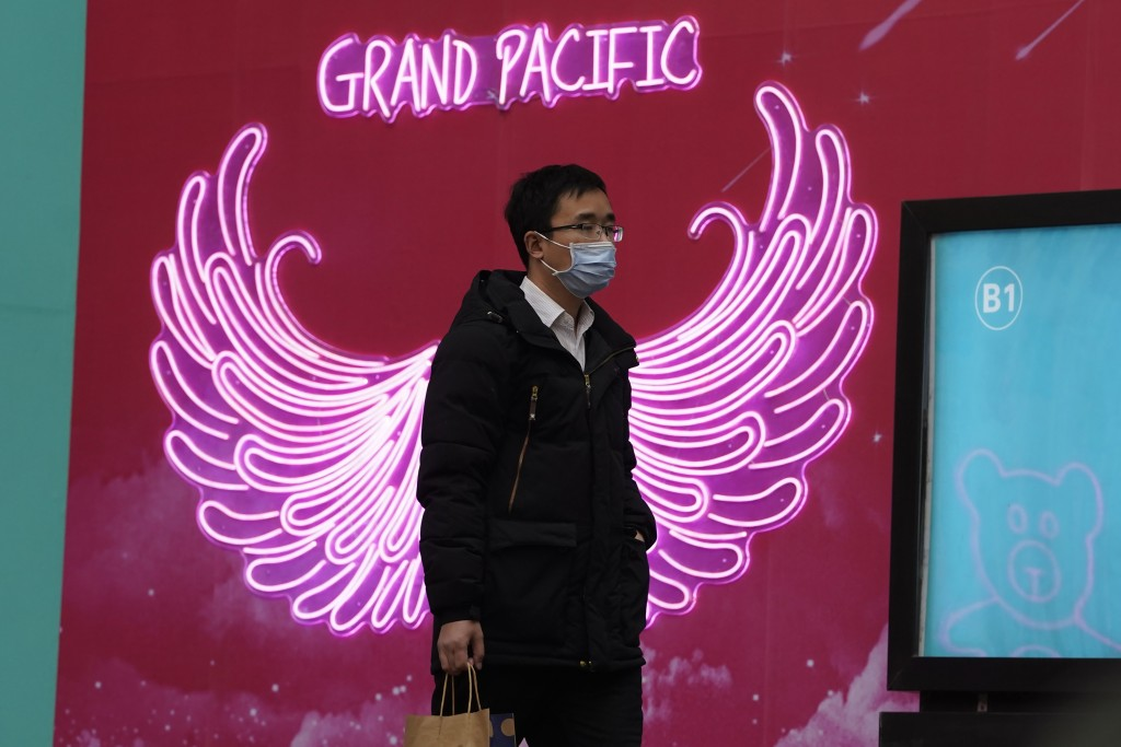 A man wearing a mask to protect from the coronavirus passes by neon lights along a retail street in Beijing Tuesday, March 2, 2021. The state of the w...