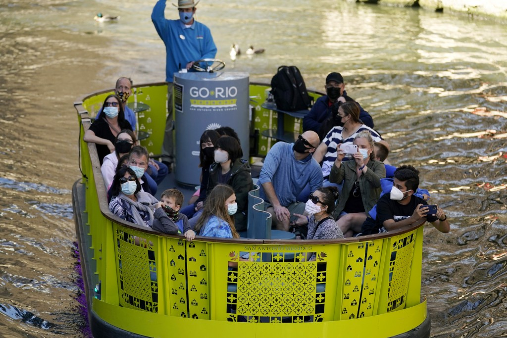 Visitors wear face masks during the coronavirus pandemic as they travel along the River Walk, Wednesday, March 3, 2021, in San Antonio. Gov. Greg Abbo...