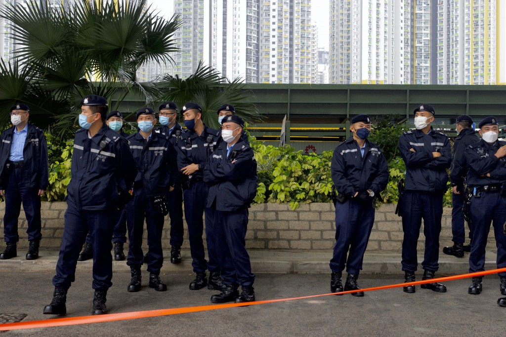 Police officers stand guard as supporters queue up for hearing outside a court in Hong Kong Thursday, March 4, 2021. A marathon court hearing for 47 p...