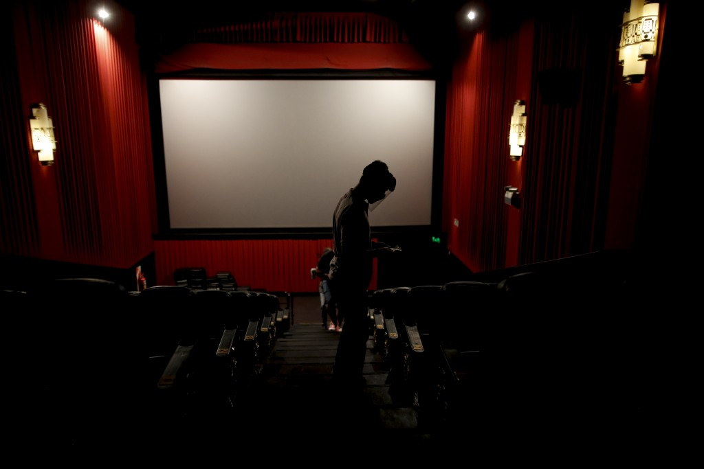 An usher looks for seats at a cinema after almost a year of theaters being closed due to the COVID-19 pandemic, in Buenos Aires, Argentina, Wednesday,...