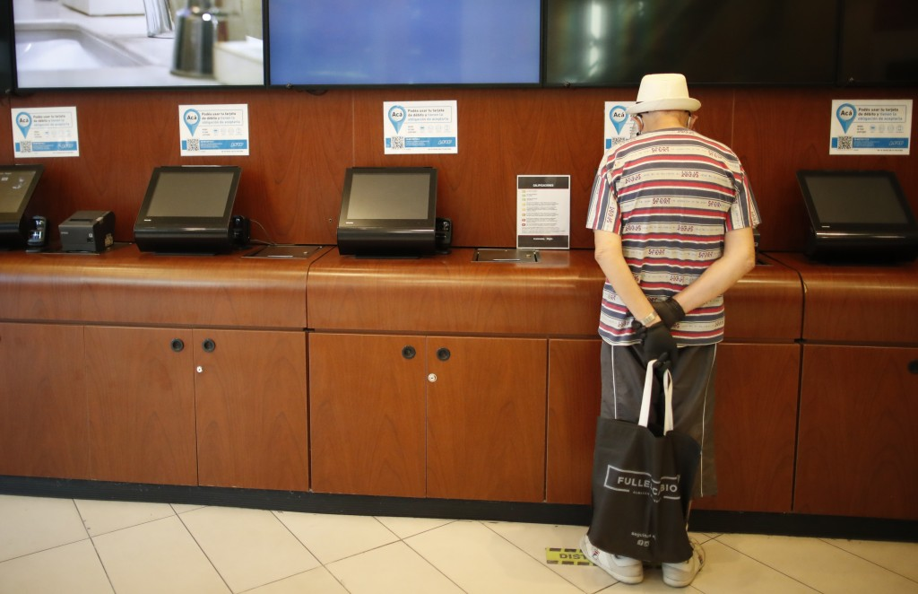 A man prepares to buy a ticket at a cinema after almost a year of theaters being closed due to the COVID-19 pandemic, in Buenos Aires, Argentina, Wedn...