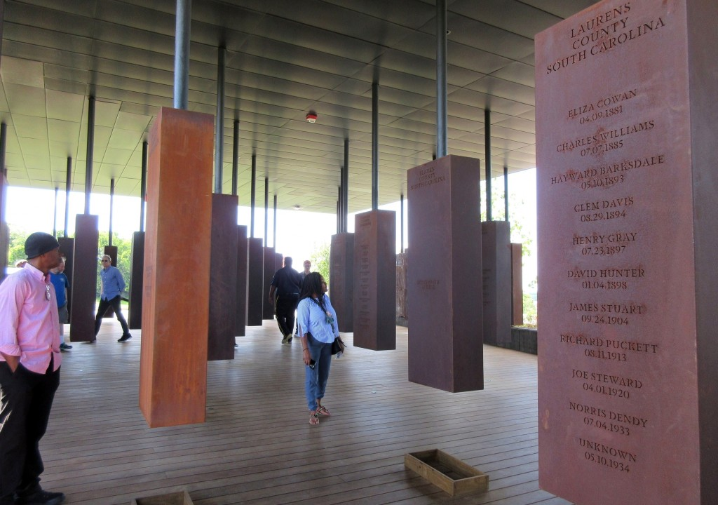 FILE - In this April 28, 2018, file photo, visitors look at markers bearing the names of lynching victims at the National Memorial for Peace and Justi...