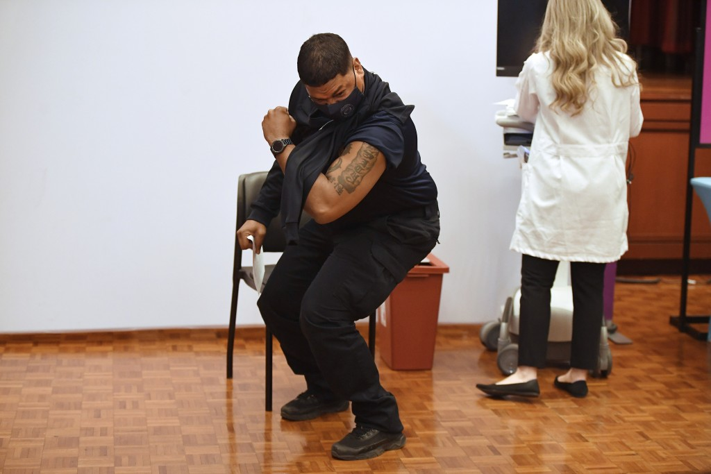 Hartford Public Schools Safety Officer Victor Rodriguez flexes his arm muscle after receiving a Johnson & Johnson COVID-19 at Hartford Hospital in Har...