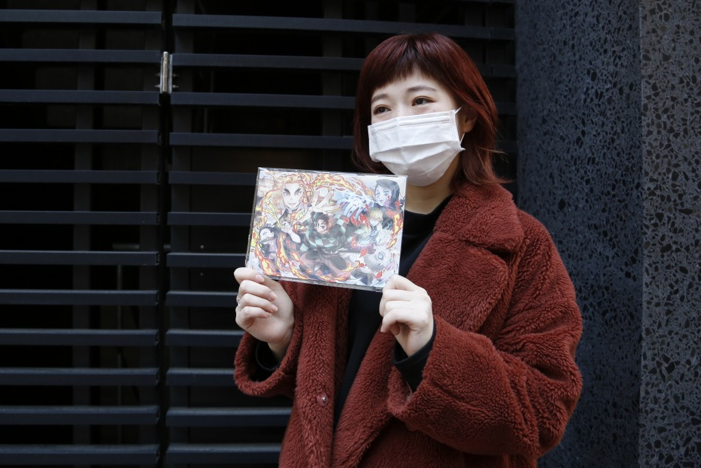 "Japanese hairstylist Akina Nasu wearing a face mask shows a picture she got when she went to see the film ""Demon Slayer,"" which has become the nation'..."