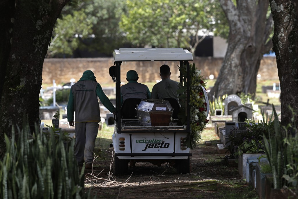 Cemetery workers transport the coffin that contains the remains of Jose Valdelirio believed to have died from the new coronavirus, to a burial site at...