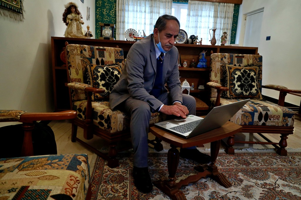 Louis Clemis reviews photos of the storming of the church on his laptop during an interview with The Associated Press in Baghdad, Iraq, Sunday, Feb. 1...