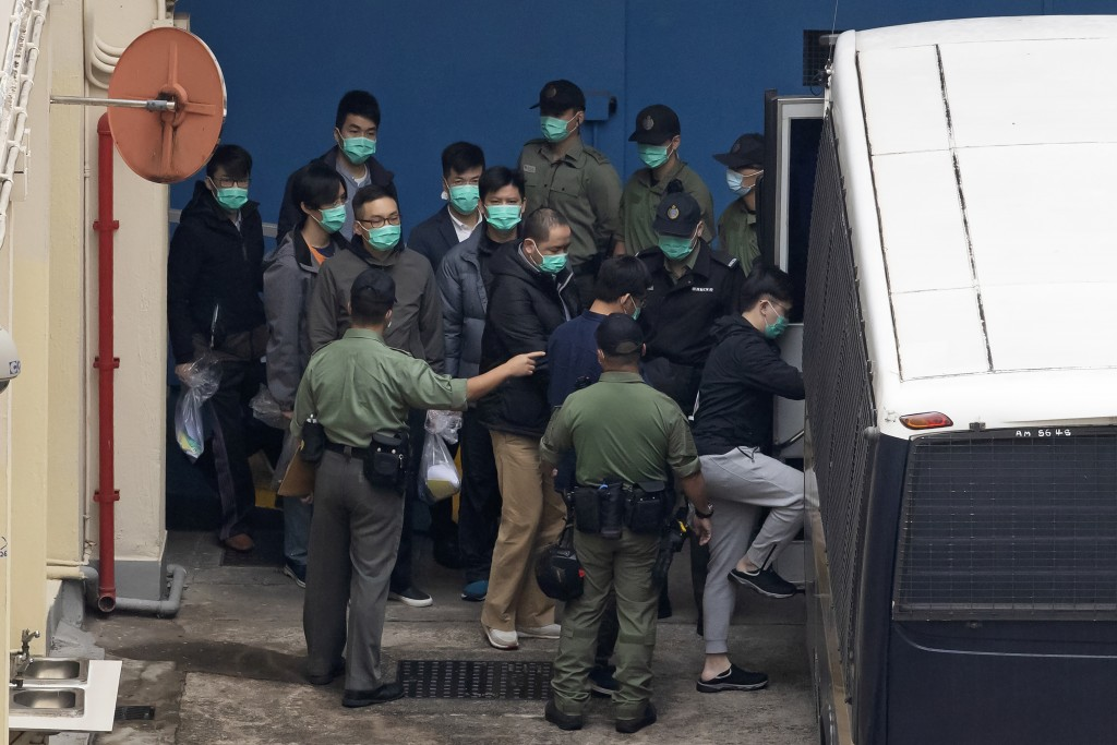 Some of the 47 pro-democracy activists are escorted by Correctional Services officers to a prison van in Hong Kong, Thursday, March 4, 2021. A maratho...
