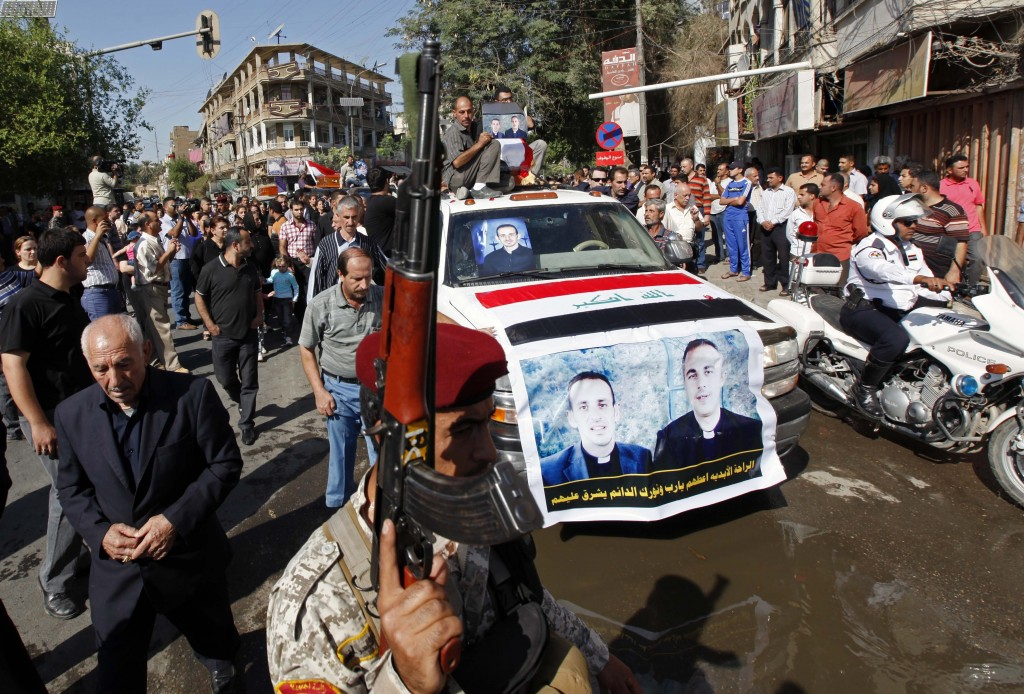 File - In this Tuesday, Nov. 2, 2010 file photo, the coffins of two slain priests and their parishioners arrive at a funeral mass in Baghdad, Iraq. Th...