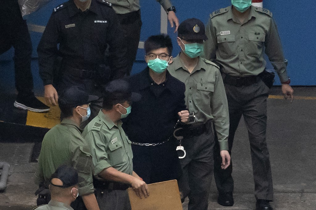 Hong Kong activist Joshua Wong, one of the 47 pro-democracy activists is escorted by Correctional Services officers to a prison van in Hong Kong, Thur...