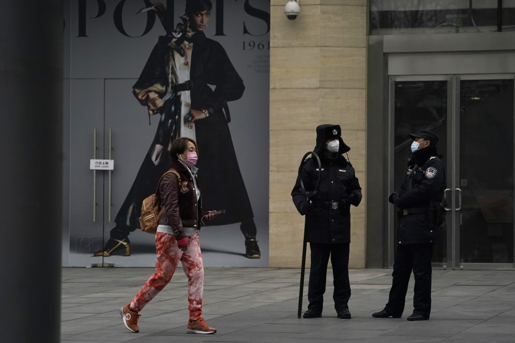 Security personnel watch over a retail street in Beijing Wednesday, March 3, 2021. The state of the world's second largest economy takes precedence am...