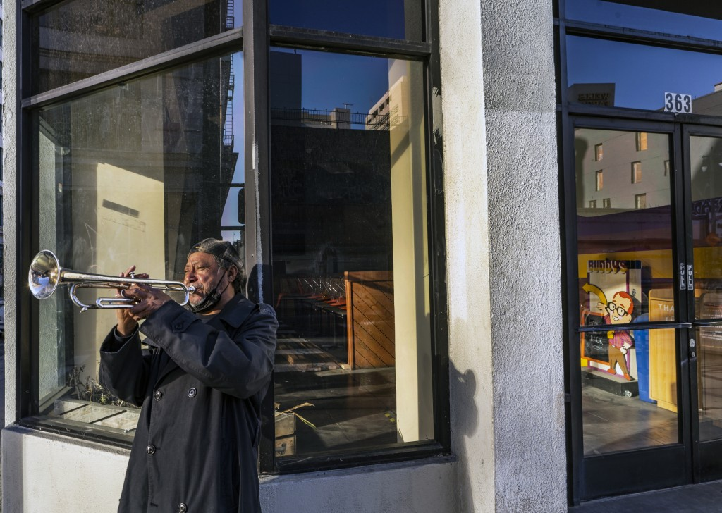 "FILE - In this Feb. 5, 2021, file photo, street musician Roberto Hernandez, originally from El Salvador, plays ""Lambada"" on his trumpet outside Buddy'..."