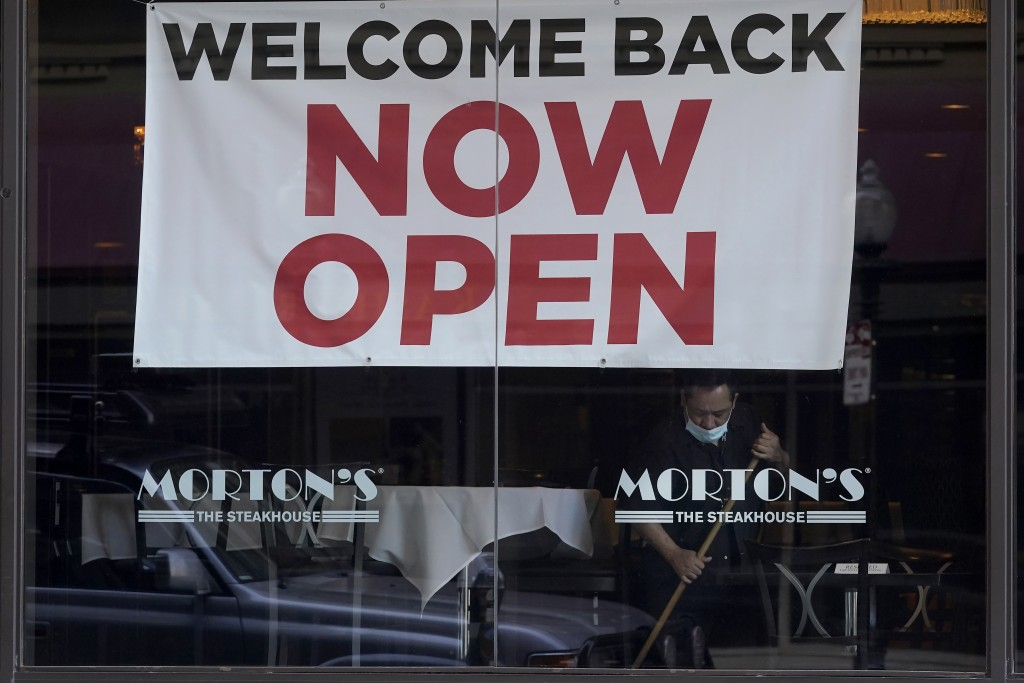 """A sign reading """"Welcome Back Now Open"""" is posted on the window of a Morton's Steakhouse restaurant as a man works inside during the coronavirus pandem..."""