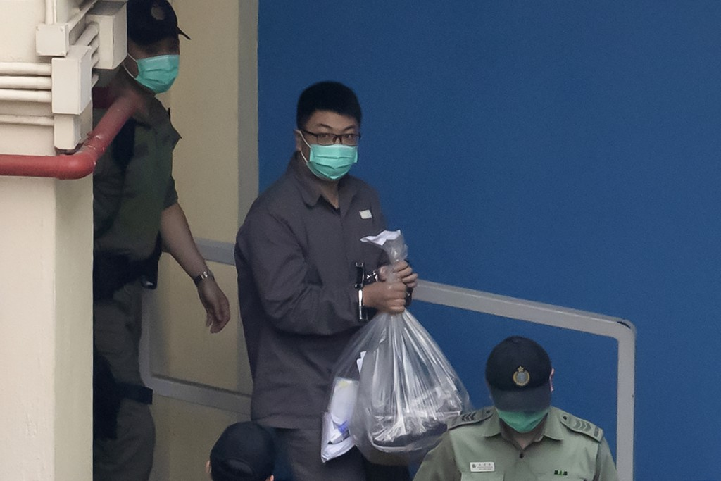 Hong Kong activist Ben Chung Kam-lun, one of the 47 pro-democracy activists is escorted by Correctional Services officers to a prison van to change to...