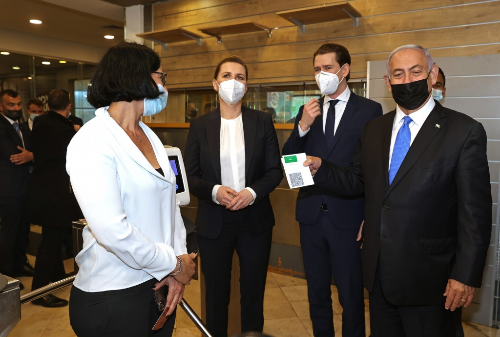 """Israeli Prime Minister Benjamin Netanyahu, right, holds a """"Green Pass,"""" for citizens vaccinated against COVID-19,  as he visits a fitness gym with Aus..."""