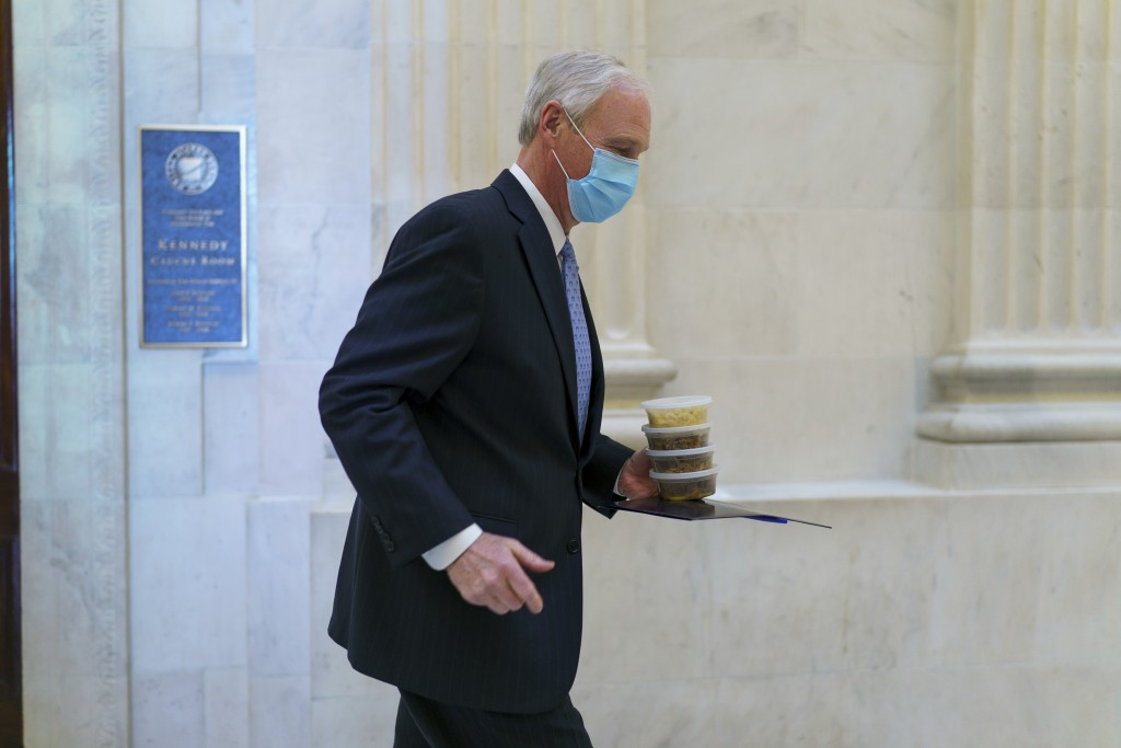 Sen. Ron Johnson, R-Wis., carries containers of food as he leaves a Senate Republican policy luncheon on Capitol Hill in Washington, Thursday, March 4...