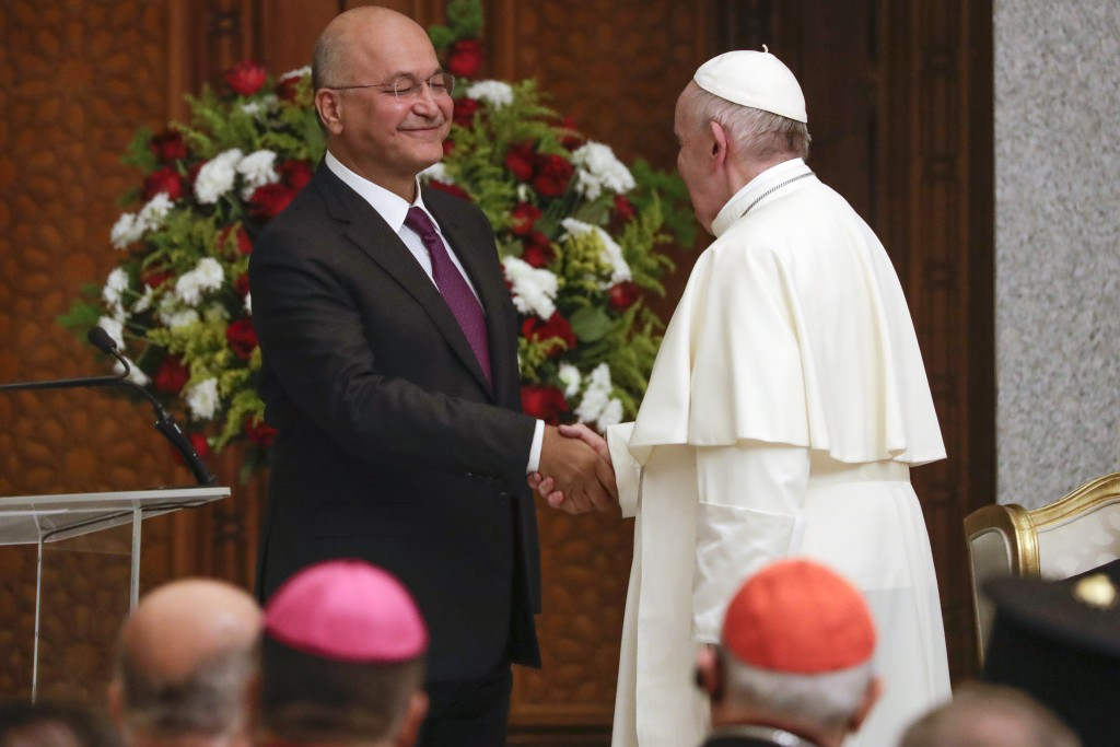 Pope Francis and Iraqi President Barham Salih shake hands, at Baghdad's Presidential Palace, Iraq, Friday, March 5, 2021. Pope Francis has arrived in ...