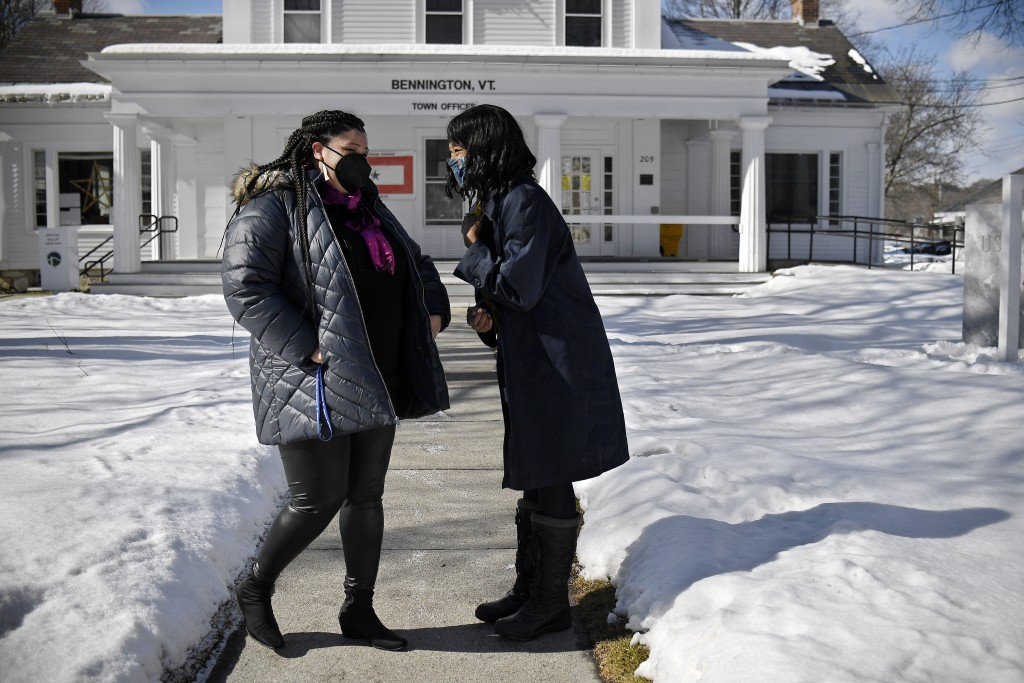 In this Saturday, Feb. 20, 2021, photo, Mia Schultz, president of the Rutland area branch of the NAACP, left, laughs with friend Tina Cook, right, out...