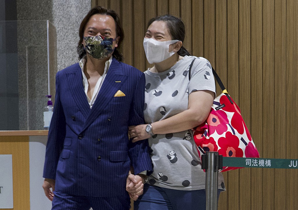 Lawrence Lau, left, one of the 47 pro-democracy activists charged with conspiracy, leaves with his relative after being released on bail outside a cou...