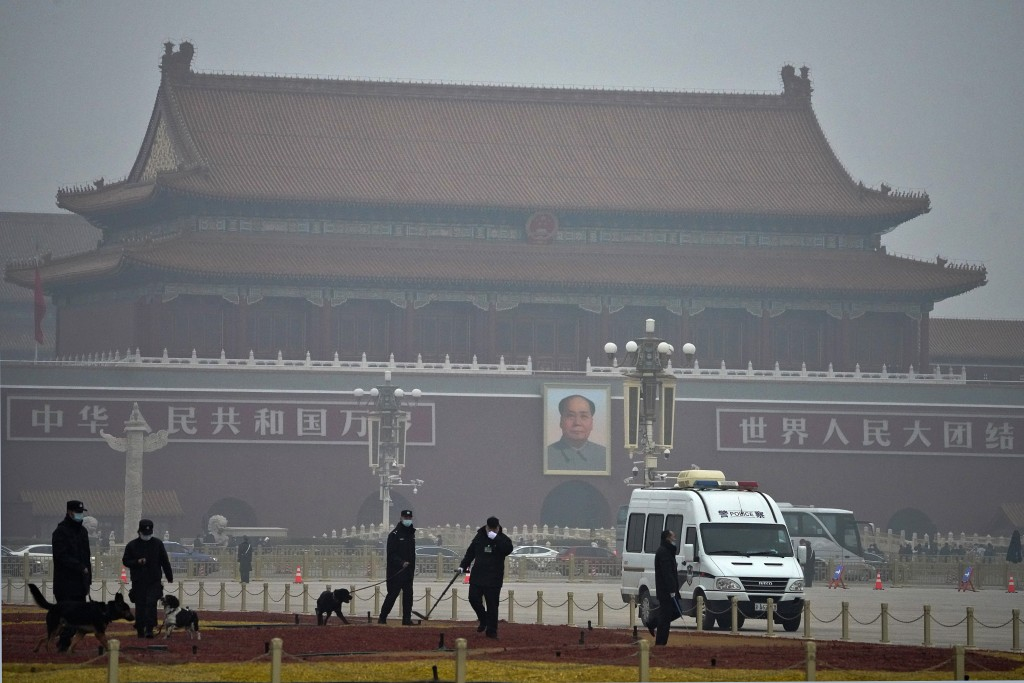Police officers use sniffer dogs to check on Tiananmen Square before delegates arrive for the opening session of China's National People's Congress (N...
