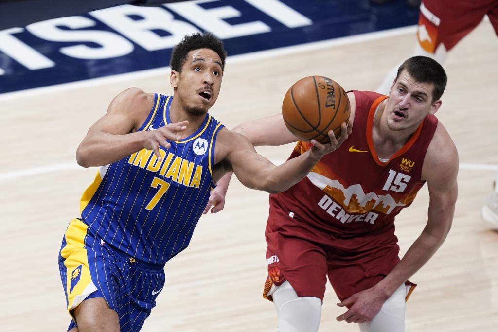 Indiana Pacers' Malcolm Brogdon (7) shoots against Denver Nuggets' Nikola Jokic (15) during the first half of an NBA basketball game, Thursday, March ...