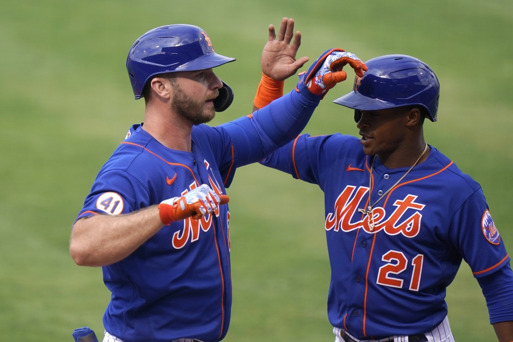 New York Mets' Pete Alonso, left, is greeted by Mallex Smith (21) after hitting a grand slam during the fifth inning of a spring training baseball gam...