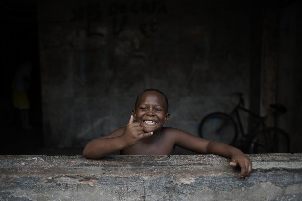 A child smiles at the camera as a non-governmental organization distributes donated food inside an occupied building that used to house a factory, ami...