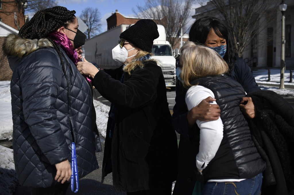In this Saturday, Feb. 20, 2021, photo, Mia Schultz, president of the Rutland area branch of the NAACP, left, is helped with a scarf made for her by f...