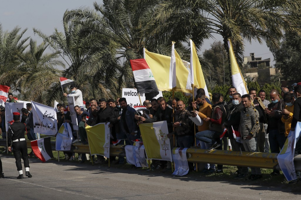 People stand by the road as they wait for Pope Francis, in Baghdad Iraq, Friday, March 5, 2021. Pope Francis heads to Iraq on Friday to urge the count...