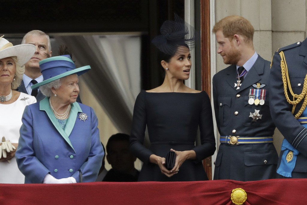 FILE - In this Tuesday, July 10, 2018 file photo Britain's Queen Elizabeth II, Meghan the Duchess of Sussex and Prince Harry stand on a balcony to wat...