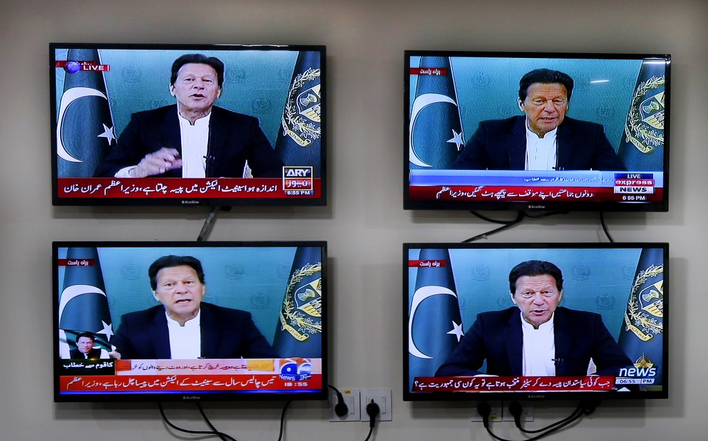 Various Pakistani news channels broadcast a live address to the nation by Pakistan's Prime Minister Imran Khan, at the office of The Associated Press,...