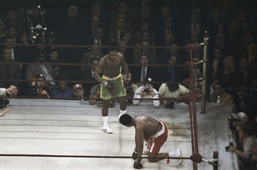 FILE - Boxer Muhammad Ali looks up towards Joe Frazier, center, during a title fight at Madison Square Garden in New York, in this March 8, 1971, file...