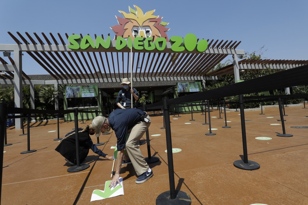 FILE - In this June 11, 2020, file photo, Devon Prince, front, puts down a sticker to guide visitors at the San Diego Zoo once it reopens, as Emmanuel...