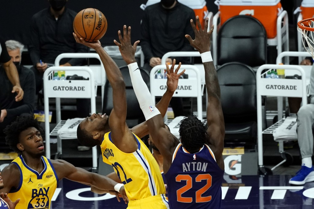 Golden State Warriors forward Andrew Wiggins (22) drives against Phoenix Suns center Deandre Ayton (22) during the first half of an NBA basketball gam...
