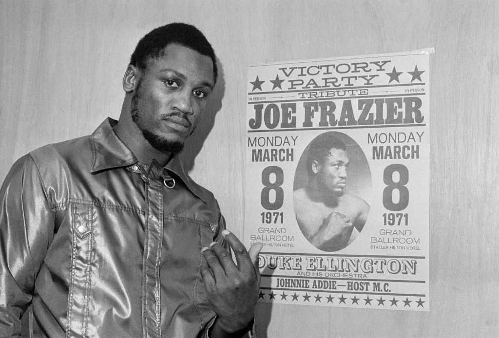"""FILE - Heavyweight champ Joe Frazier poses by a poster advertising his """"victory party"""" as he leaves his dressing room after a final public workout in ..."""