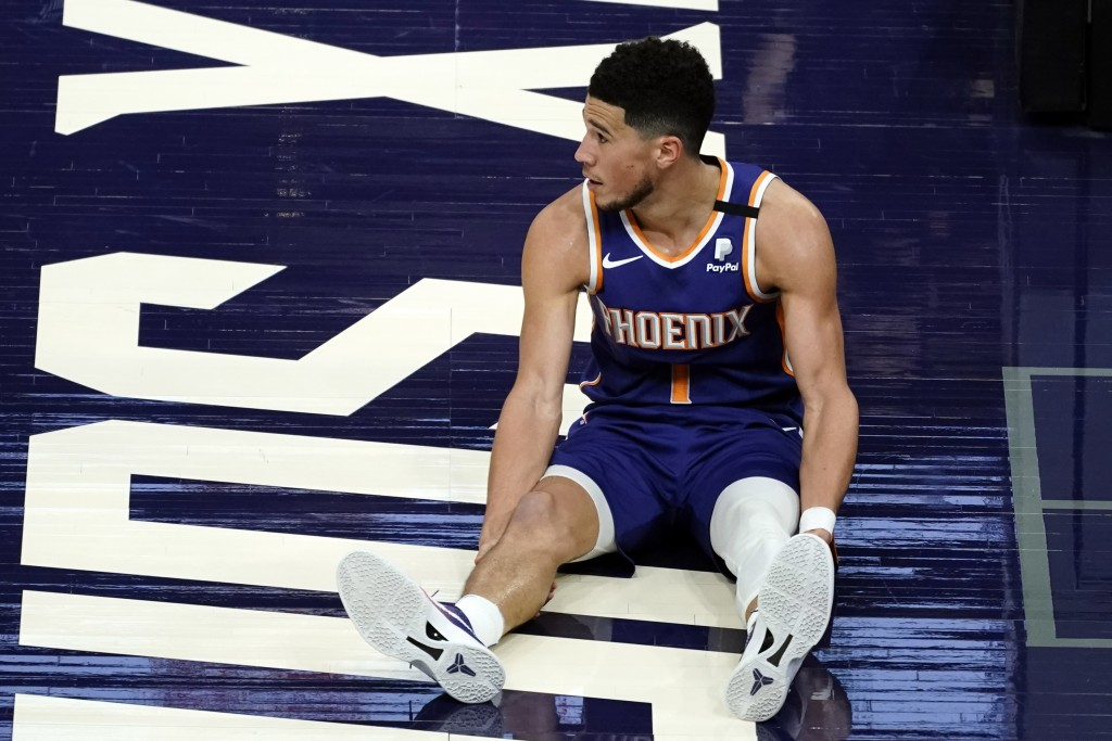 Phoenix Suns guard Devin Booker watches as play continues after he was knocked to the floor during the second half of the team's NBA basketball game a...