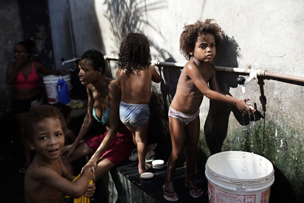 Children bathe as a non-governmental organization distributes donated food inside an occupied building that used to house a factory, amid the new coro...
