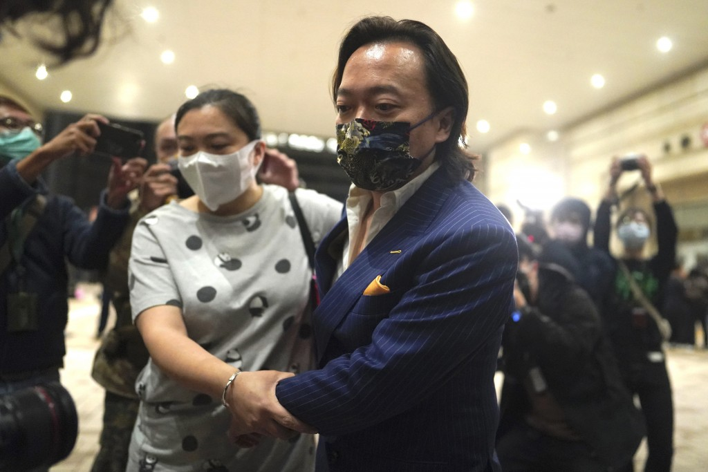 Lawrence Lau, charged with conspiracy, and his relative leave after being released on bail at a court in Hong Kong, Friday, March 5, 2021. Four of the...