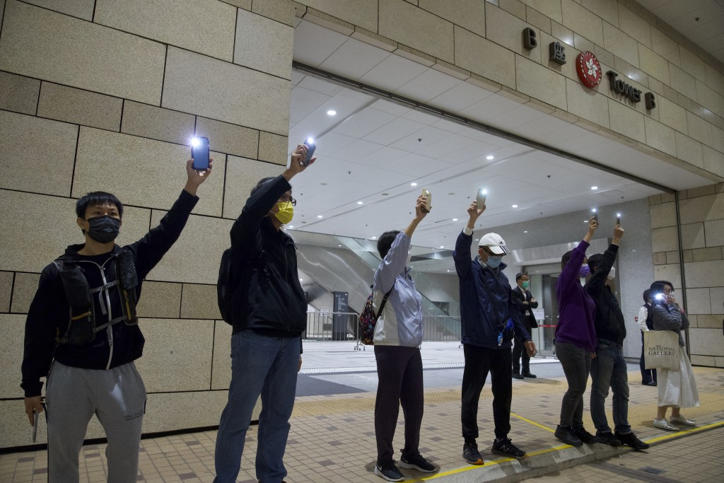Supporters of the 47 pro-democracy activists charged with conspiracy wave mobile phone lights outside a court in Hong Kong, Friday, March 5, 2021. Fou...