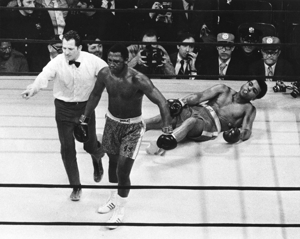 FILE - In this March 8, 1971, file photo, boxer Joe Frazier is directed to his corner by referee Arthur Marcante after knocking down Muhammad Ali duri...