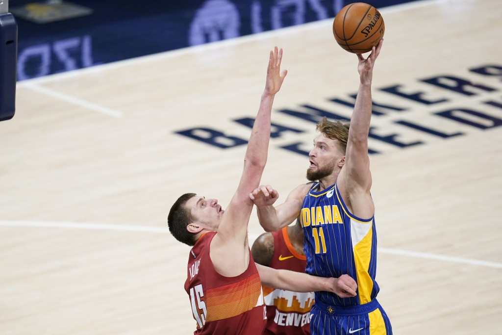 Indiana Pacers' Domantas Sabonis (11) shoots over Denver Nuggets' Nikola Jokic (15) during the first half of an NBA basketball game, Thursday, March 4...