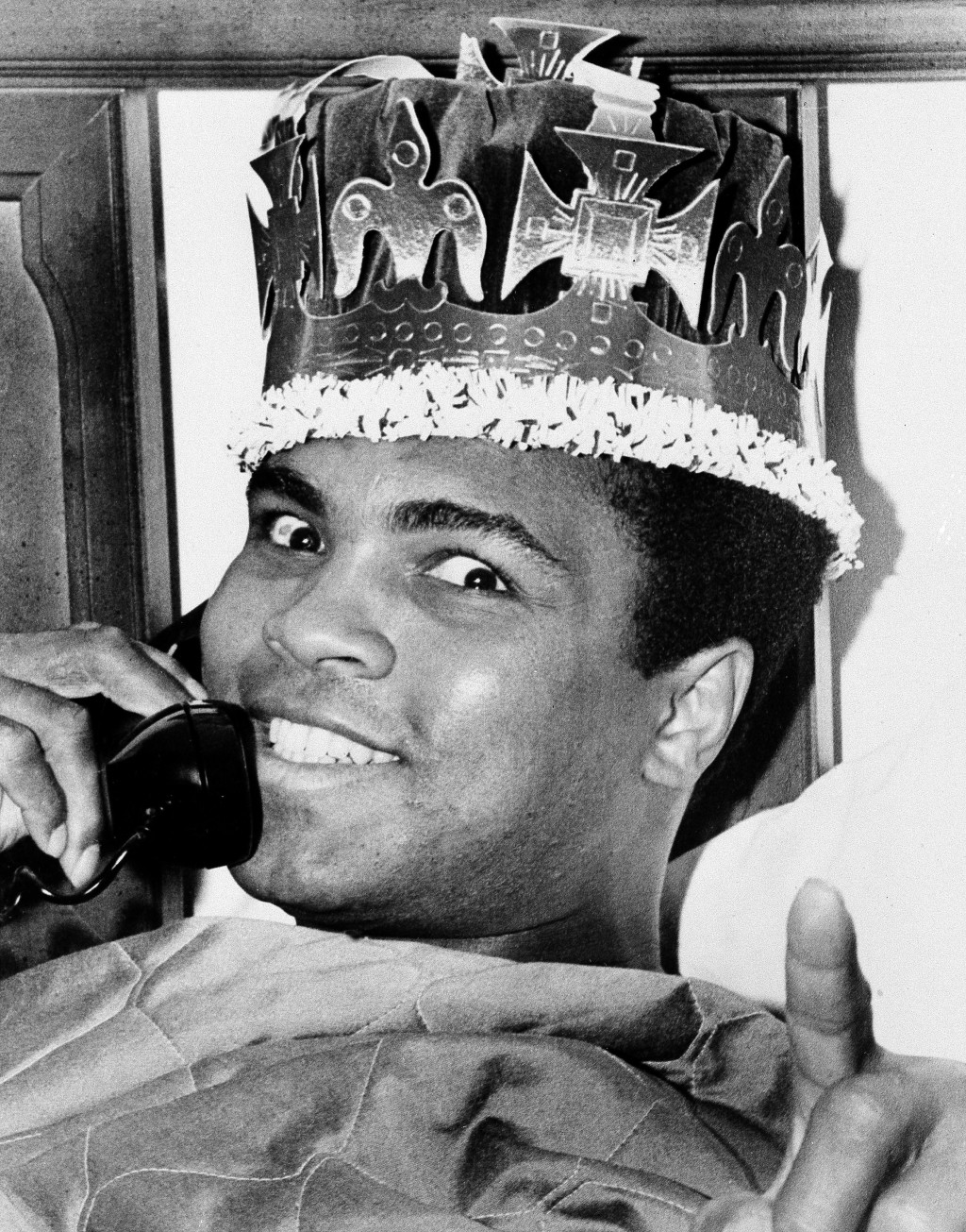 FILE - Muhammad Ali wears a crown while speaking on the phone in Miami Beach, Fla., ahead of his March 8 fight against Joe Frazier in New York, in thi...