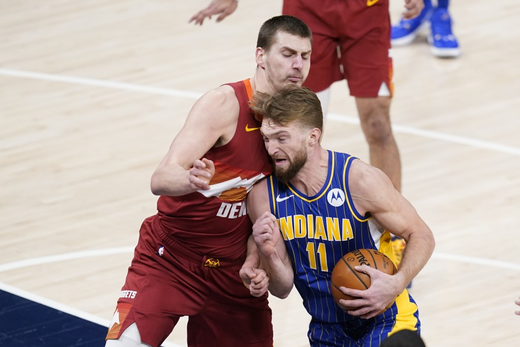 Indiana Pacers' Domantas Sabonis (11) goes to the basket against Denver Nuggets' Nikola Jokic (15) during the first half of an NBA basketball game, Th...