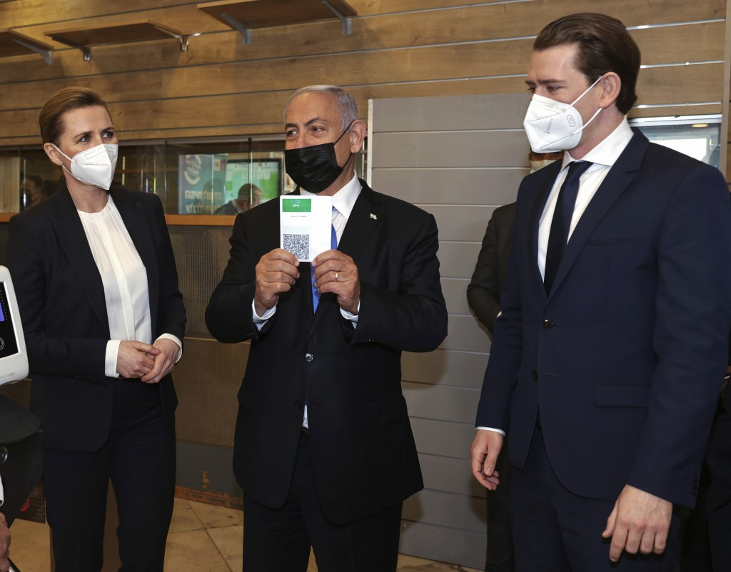 """Israeli Prime Minister Benjamin Netanyahu, center, holds a """"Green Pass,"""" for citizens vaccinated against COVID-19,  as he visits a fitness gym with Au..."""