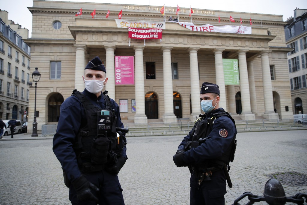 Police officers stand outside the occupied iconic Odeon theater, Friday, March 5, 2021 in Paris. Out-of-work French culture and tourism workers have o...