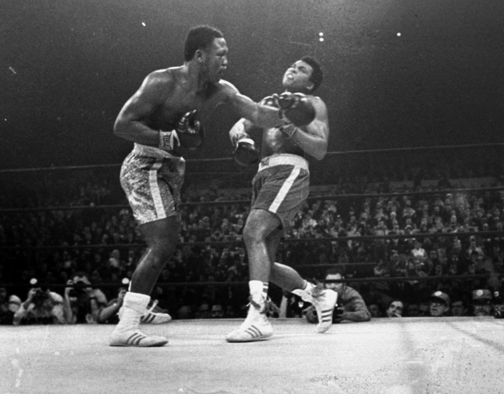 FILE - Joe Frazier hits Muhammad Ali with a left during the 15th round of their heavyweight title fight at New York's Madison Square Garden, in this M...