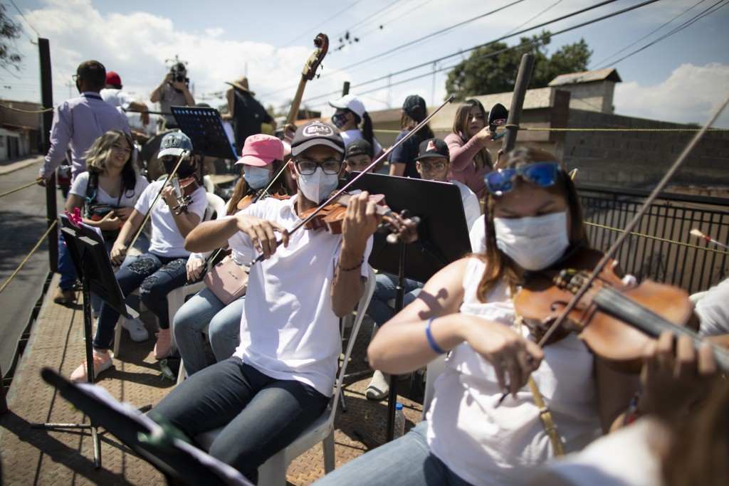 Wearing masks to curb the spread of the new coronavirus, musicians join pianist, composer and conductor Jose Agustin Sanchez on the bed of an eighteen...