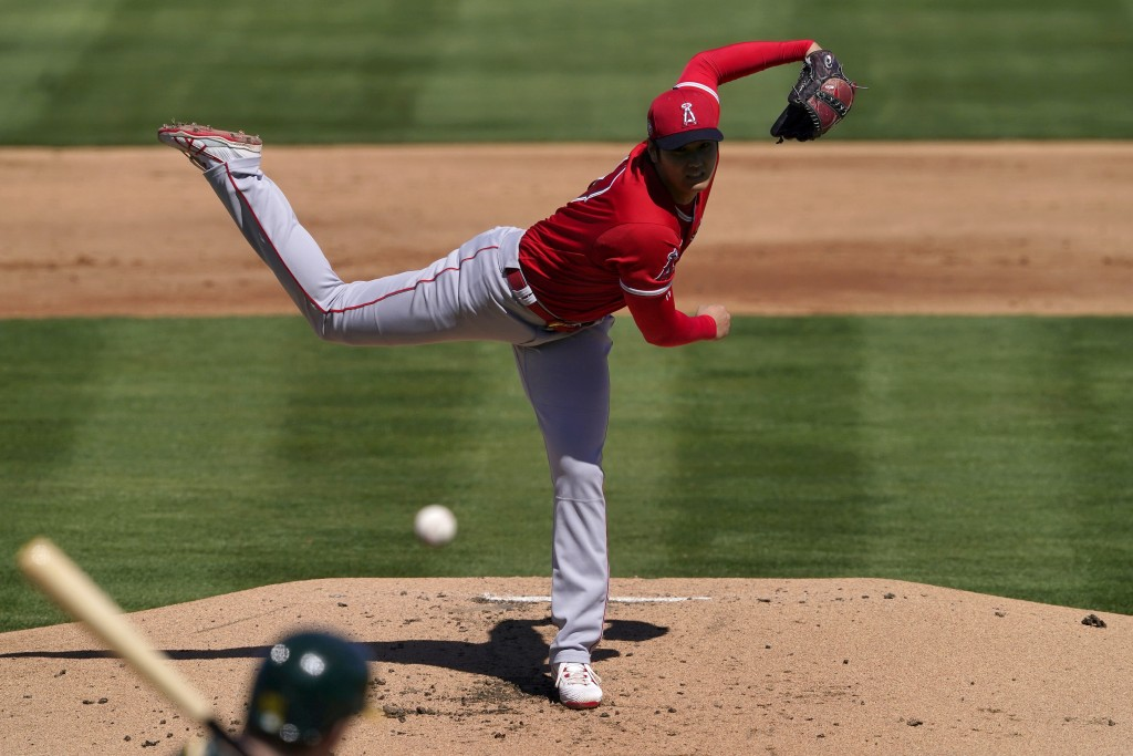 Los Angeles Angels pitcher Shohei Ohtani (17) throws against the Oakland Athletics during the first inning of a spring training baseball game, Friday,...